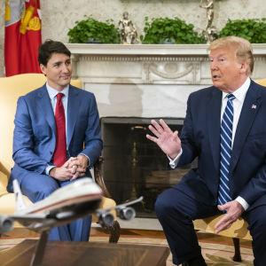 Donald Trump håller ordet med utsträckta händer tillsammans med leende Justin Trudeau.