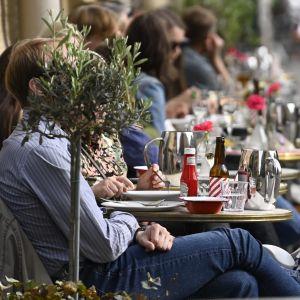 Ihmisiä nauttimassa lämpimästä säästä The Cock -ravintolan terassilla Helsingissä 3. kesäkuuta 2021.