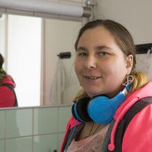Tintti hymyilee kameralle siivouksen lomassa kylpyhuoneen peilin edessä.