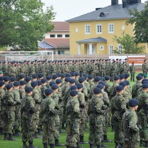 Militärparad med rekryter ute på en gräsplan.