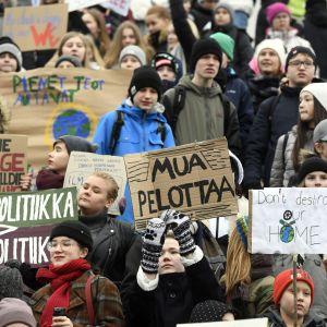 Unga håller upp demonstrationsplakat under klimatstrejk i Helsingfors.