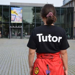 En kvinna med röd halare och en svart t-skjorta med texten tutor på ryggen står på Arkens gård.