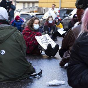 Elokapina mielenosoittajat istuvat kadulla.