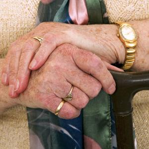 En äldre persons händer på en käpp.