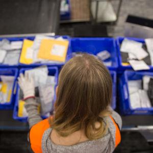 Postanställd sorterar paket