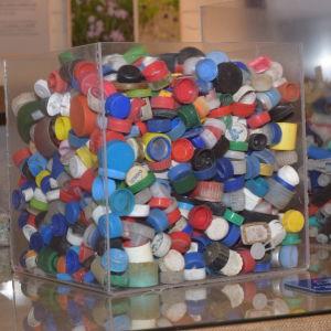 En glasskål modell större full med gamla plastkapsyler.