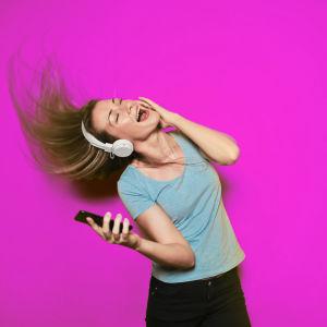 Nainen kuuntelee musiikkia ja laulaa