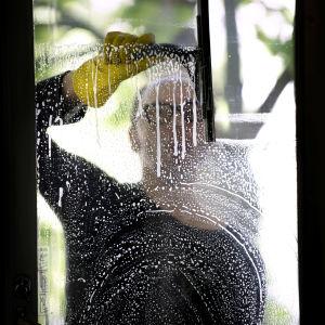 Mies pesee parvekeoven lasia.