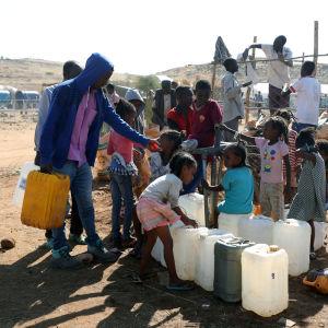 Lapset keräävät vettä kanistereihin Um Rakuban pakolaisleirillä Sudanissa.