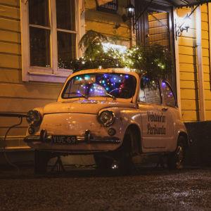 En gammaldags bil dekorerad med julbelysning och grankvistar