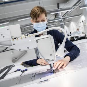 Ompelija Anna Laamo VA-Varuste Oyn: tehdastiloissa ompelemassa veneen kuomuja.