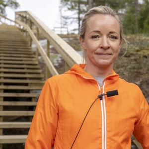 Kvinna står framför motionstrappa.