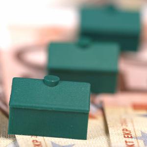 Tre gröna Monopolhus i rad på eurosedlar.