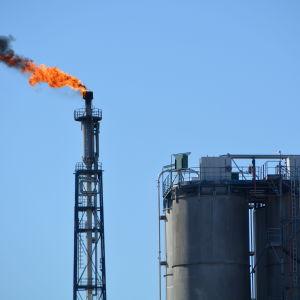 Fackla med orange eld och svart rök, klarblå himmel.