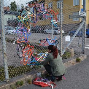 Johanna Kunelius hänger upp galgar i pansarnätet. Bokstaven G syns med galgar i olika färger.