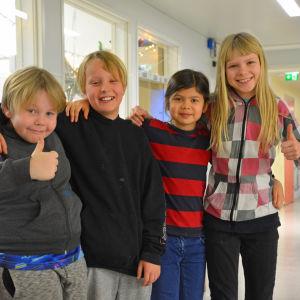 Fyra barn i en skolkorridor.