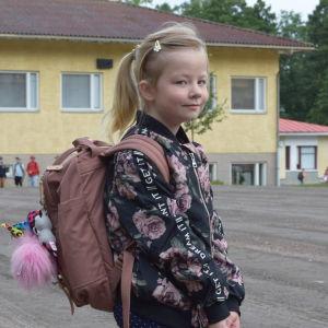 Förstaklassaren Emma Forsström utanför Kyrkfjärdens skola i Ingå.