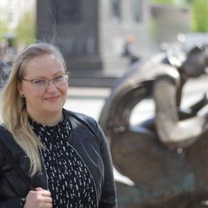 Vit kvinna med långt blont hår står framför en skulptur av Erikki Kannosto.
