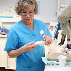 Sairaanhoitaja Tuula Mäenpää työssään vastaanottohuoneessa Hämeenlinnan Ojoisten terveysasemalla.