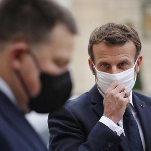 Emmanuel Macron rättar till sitt munskydd med ena handen när han stiger ur en bil.