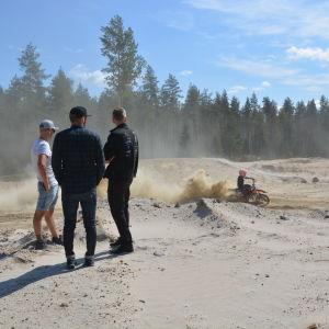 Tre män står och tittar på en motocrossförare som kör.