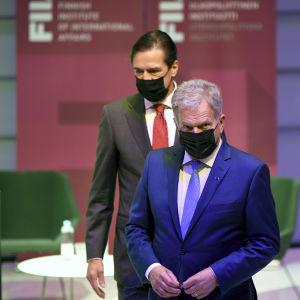 Sauli Niinistö esiintyi Ulkopoliittisen instituutin Forum tapahtumassa 29. syyskuuta. Kävelee maski kasvoillaa, taustalla muita osallistujia.