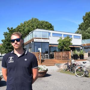 Man står med solglasögon på framför en byggnad som är byggd av baracker