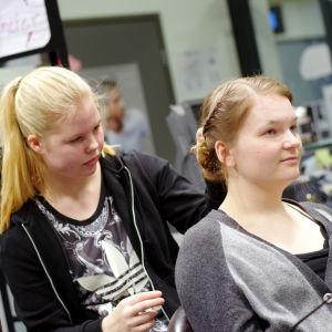 Frisörstuderanden Elin Sigfridsson jobbar på en uppsättning i Wilma Westerlunds hår.