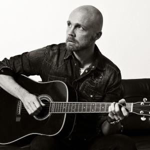Juha Tapio istuu sohvalla ja soittaa kitaraa.