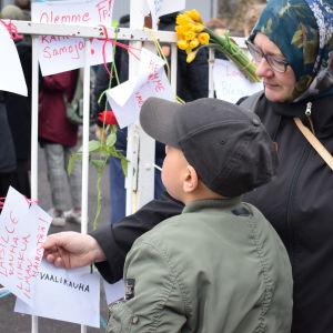 Tuula Mohamud med sin son tittar på budskap hängda på staketet vid moskén i Melluingsbacka.