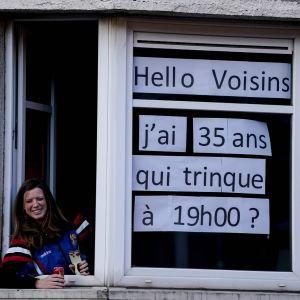 En kvinna med en skylt i fönstret där det står: Jag fyller 35 år i dag. Vem skålar med mig klockan 19. På grund av utegångsförbudet har belgier inte möjlighet att samlas i grupper.
