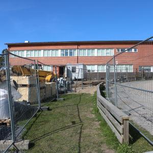 En röd tegelbyggnad. Framför byggnaden finns en gång med stängslen på båda sidor som leder upp till byggnaden.