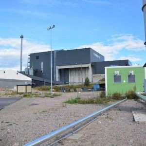 En svart byggnad med en grön container i förgrunden.