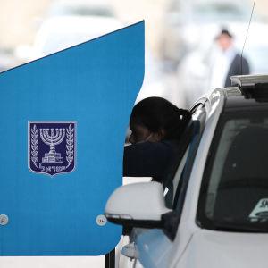 En kvinna sträcker sig ur sin bil för att rösta.