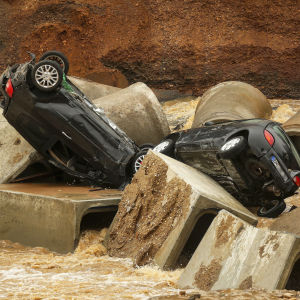 Bilar som svepts med av vattenmassor.
