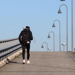 En ungdom går ensam över en tom bro.