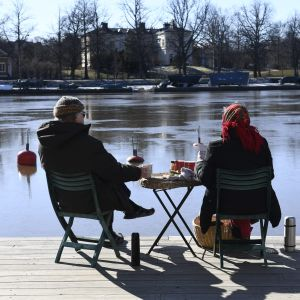 Två personer sitter på stolar med ett litet bord med mat emellan sig. Personerna blickar mot Kajsaniemi i Helsingfors.