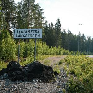 En asfalterad väg i en skog och en skylt där det står Laajametsä/Långskogen.