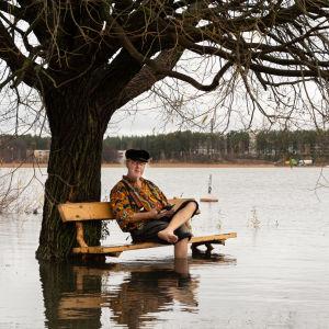 En äldre man sitter på en parkbänk som finns mitt i havet. Hans fötter är i vattnet.