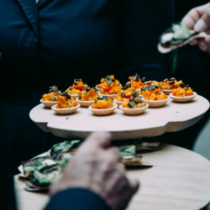 Orange-coloured bite-size snacks on a wooden plate.