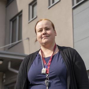 Sosionomi Jenni Koppi hymyilee kameralle Koisorannan päivystyksen pihalla.