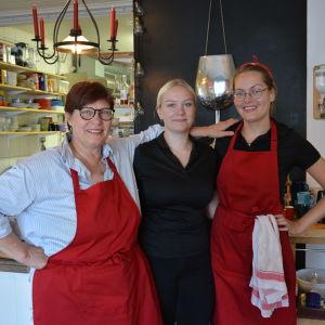 Tre kvinnor står i en restaurang, två har röda förkläden.