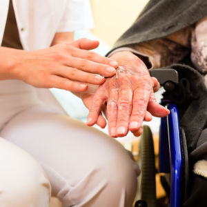 Vårdare håller äldres hand.