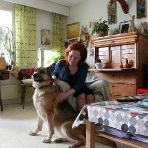 Lena Bengtson sitter i sitt vardagsrum med schäferhunden Alice bredvid sig.