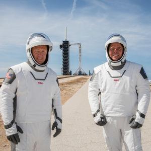 Astronauterna Douglas Hurley (t.v.) och Robert Behnken (t.h.) poserar inför avfärden med Space X rymdraket Falcon 9 i bakgrunden.