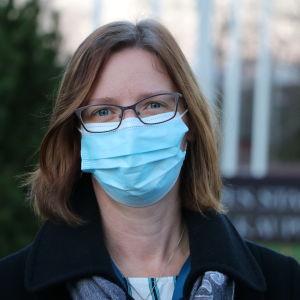 En kvinna med axellångt brunt hår. Hon har ett munskydd på ansiktet.