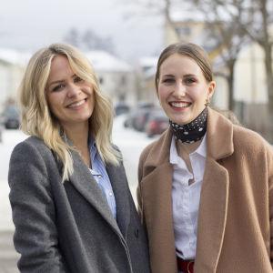 Två kvinnor står ute på en gata. Michelle till vänster i bild har långt blont hår och skrattar. Sandra till höger har håret i hästsvans ler stort.