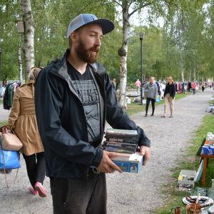 Ville Arki står och håller i en hög med grejer som han har köpt på Städdagen.