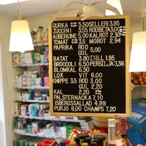En prislista i en bybutik, med fulla hyllor av hushållsvaror i bakgrunden.