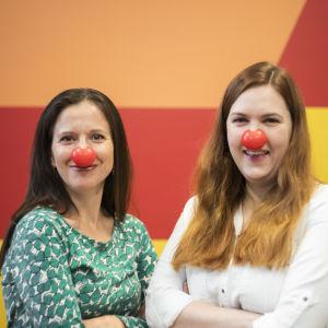 Två kvinnor står framför en färggrann bakgrund. De har clownnäsor på sig. De skrattar och ser in i kameran.